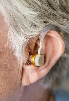 Une femme âgée portant un appareil auditif
