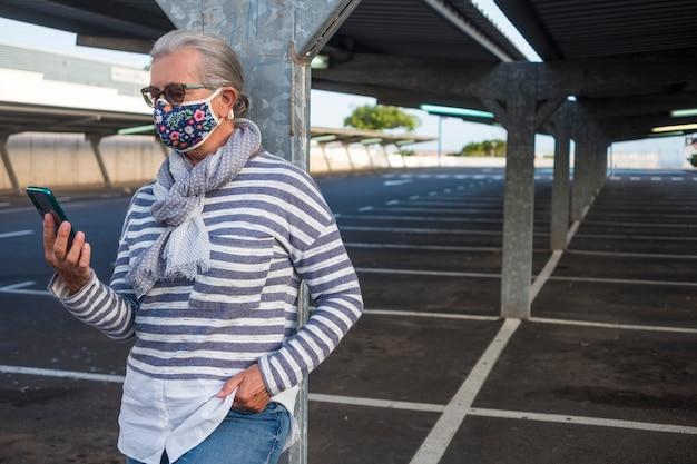 Une femme âgée portant un masque médical fleuri debout dans un parking désert regardant un téléphone intelligent