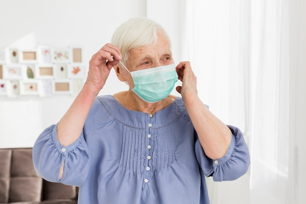 Femme âgée portant un masque médical à la maison