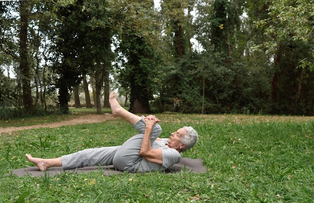 Femme âgée pratiquant le yoga en plein air