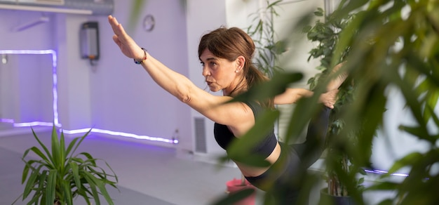 Une femme âgée pratique le yoga dans la salle de sport
