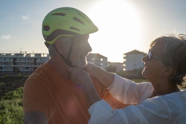 La femme âgée prend soin de son mari cycliste en mettant son casque. lumière vive du coucher du soleil