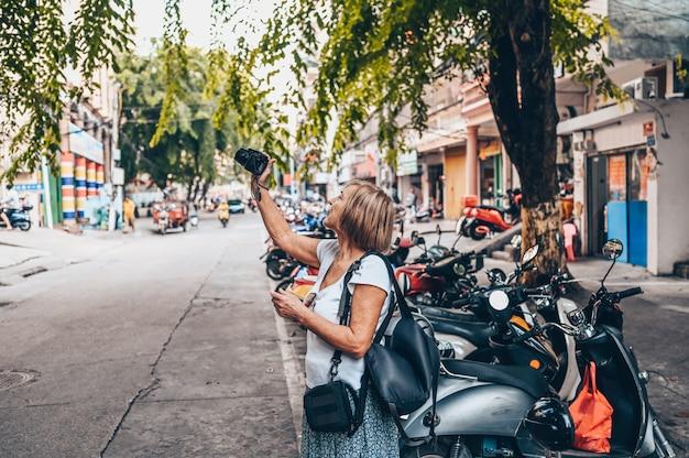 Femme âgée, prendre photos, dans rue