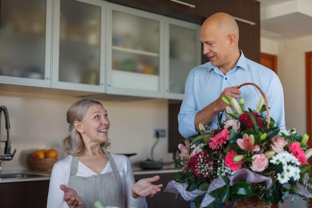 Une femme âgée prépare le dîner et un jeune homme lui offre des fleurs pour la fête des mères.