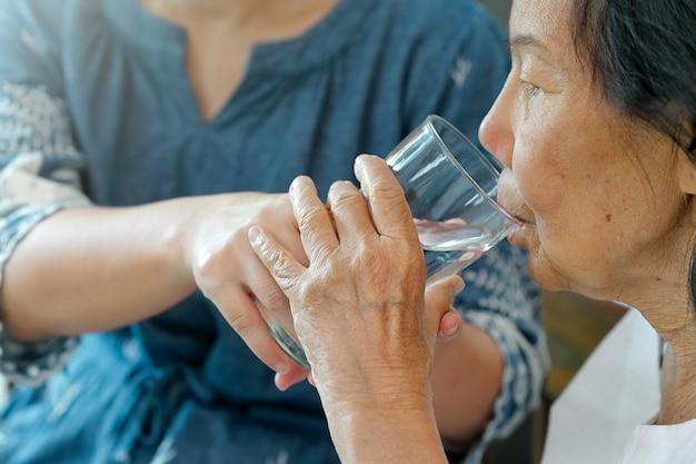 Une femme âgée reçoit un verre d'eau du soignant