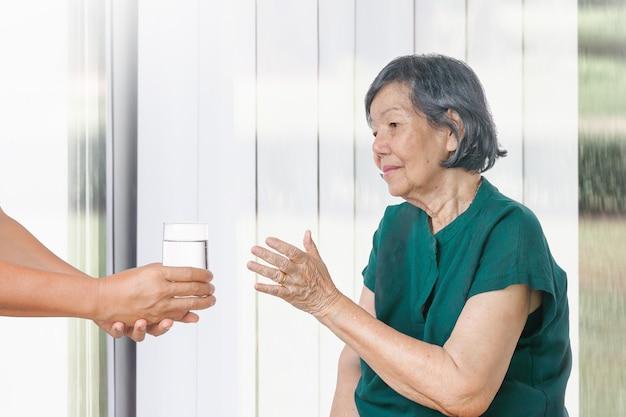Une femme âgée reçoit un verre d'eau d'un soignant