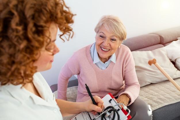 Une femme âgée reçoit la visite de son médecin ou de son soignant.