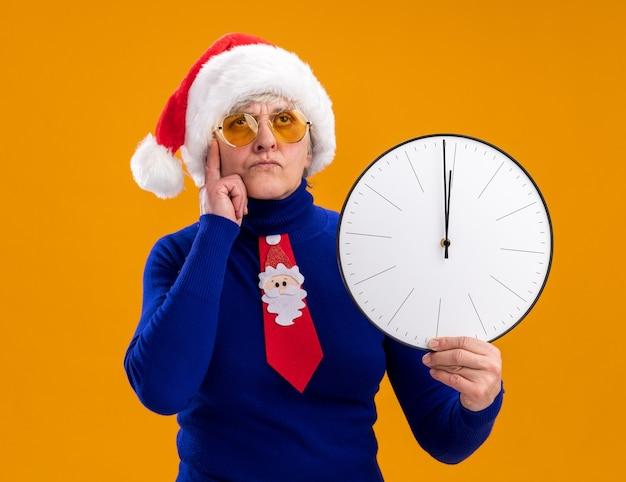 Une femme âgée réfléchie dans des lunettes de soleil avec un bonnet de noel et une cravate de noel met le doigt sur le temple et tient une horloge isolée sur un mur orange avec un espace de copie
