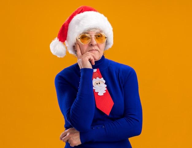 Une femme âgée réfléchie dans des lunettes de soleil avec un bonnet de noel et une cravate de noel met la main sur le menton et regarde le côté isolé sur un mur orange avec espace de copie