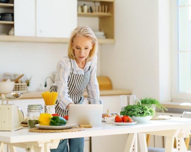 Femme âgée regardant des cours de cuisine en ligne ou des recettes vidéo tout en cuisinant à la maison dans un style moderne