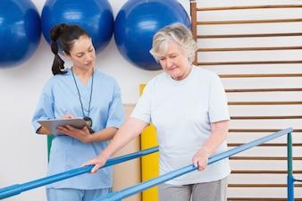 Femme âgée regardant thérapeute marchant avec des barres parallèles