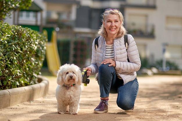 Femme âgée retraité marche parc petit chien blanc.