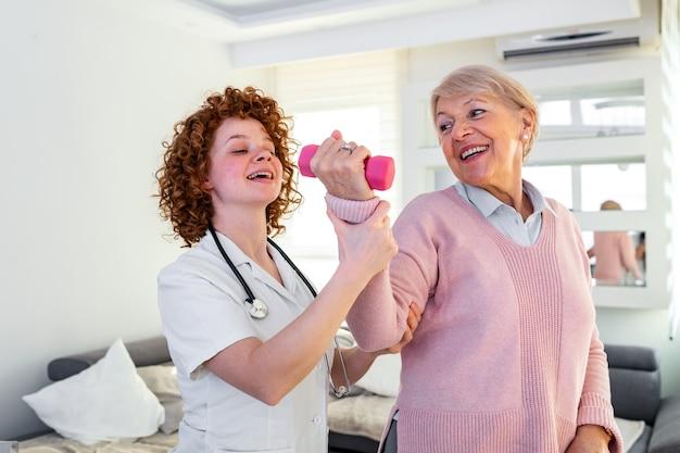 Femme âgée retrouvant une bonne santé. infirmière physiothérapeute aidant une femme âgée en réadaptation physique