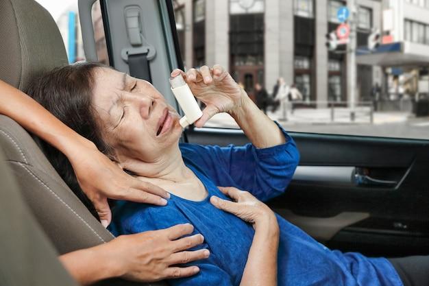 Femme âgée s'étouffant et tenant un spray contre l'asthme à l'intérieur de la voiture sur le chemin