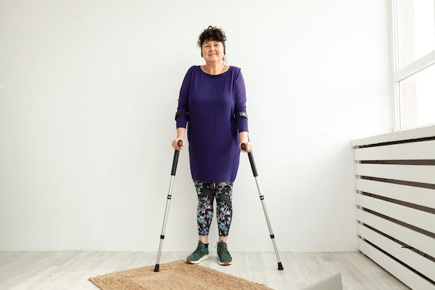 Femme âgée se dresse sur des béquilles dans le bureau du physiothérapeute. concept de récupération et de réadaptation après un traumatisme.