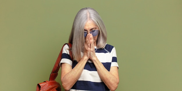 Femme âgée se sentant inquiète, pleine d'espoir et religieuse, priant fidèlement avec les paumes pressées