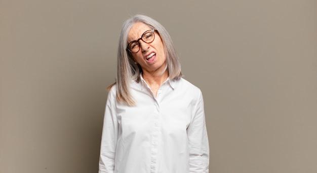 Femme âgée se sentant perplexe et confuse, avec une expression stupide et abasourdie en regardant quelque chose d'inattendu