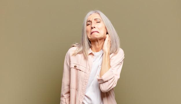 Femme âgée se sentant stressée, frustrée et fatiguée, se frottant le cou douloureux, avec un regard inquiet et troublé