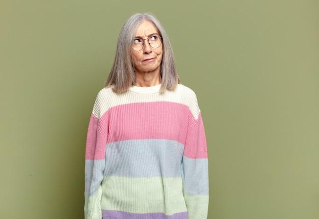 Femme âgée se sentant triste, bouleversée ou en colère et regardant de côté avec une attitude négative, fronçant les sourcils en désaccord