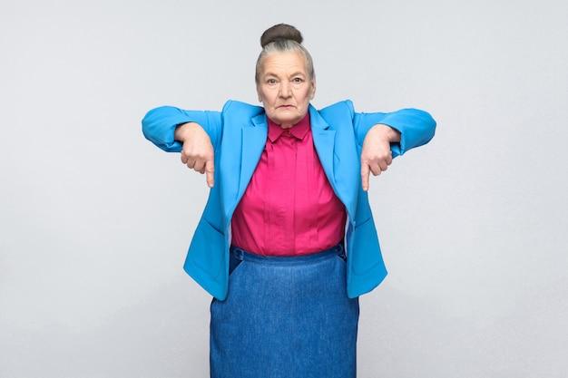 Femme âgée sérieuse pointant du doigt l'espace de copie