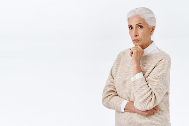 Une femme âgée sérieuse, réfléchie, intelligente et élégante, soignée avec des cheveux gris peignés, porte une tenue de fantaisie, touche le menton et regarde la caméra pensive, pensant à ce que faire ou choisir, mur blanc