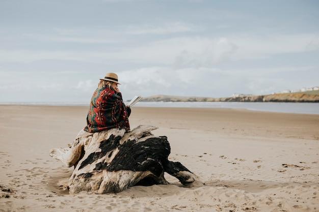 Femme âgée solitaire lisant un livre sur la plage