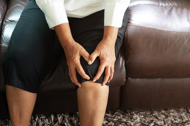 Femme âgée souffrant de douleur au genou à la maison, notion de problème de santé