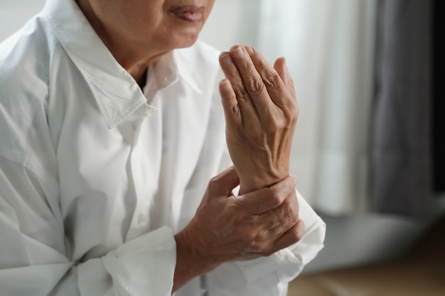 Femme âgée souffrant de douleurs de la polyarthrite rhumatoïde