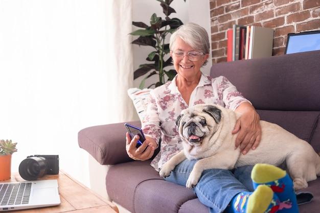 Femme âgée souriante assise sur un canapé à la maison avec un vieux chien carlin allongé sur ses jambes à l'aide d'un téléphone portable