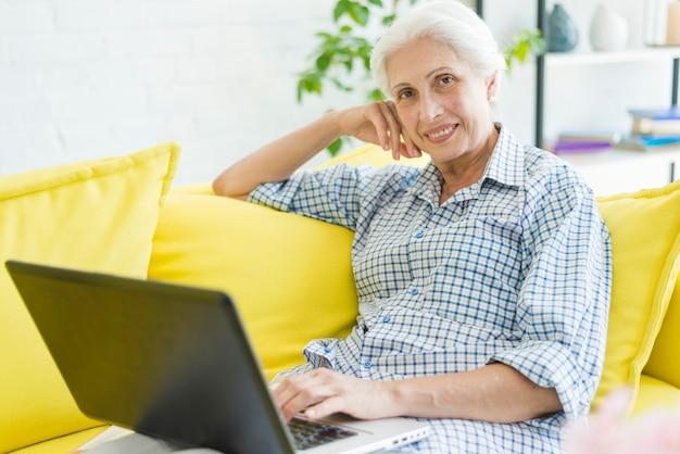 Femme âgée souriante assise sur un canapé avec ordinateur portable