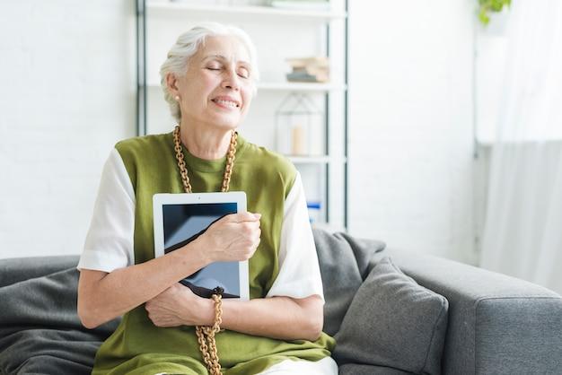 Femme âgée souriante assise sur un canapé tenant une tablette numérique