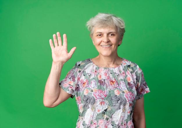 Femme âgée souriante lève la main isolée sur le mur vert