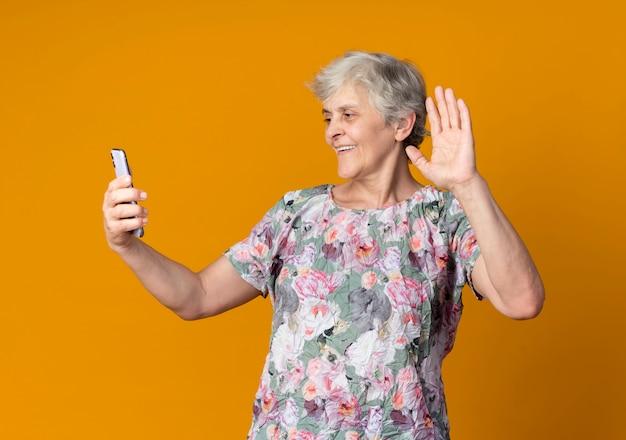 Femme âgée souriante lève la main tenant et regardant le téléphone isolé sur le mur orange