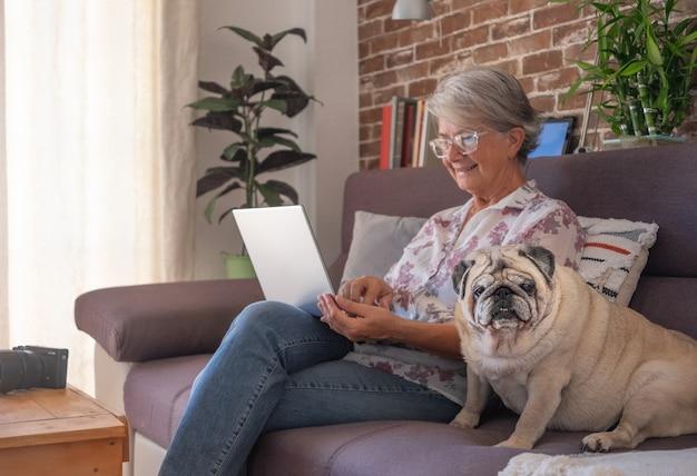 Femme âgée souriante à la maison travaillant avec un ordinateur portable, assise près de son vieux chien carlin