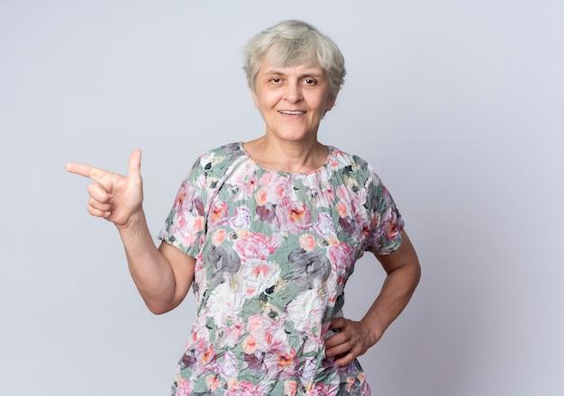 Femme âgée souriante met la main sur la taille en pointant sur le côté isolé sur un mur blanc