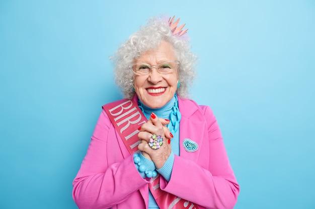 Une femme âgée souriante et optimiste serre les mains et a l'air heureuse, porte un costume de fête pour une occasion spéciale
