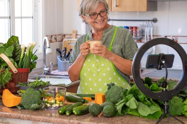 Une femme âgée souriante prend une pause-café après un cours de cuisine végétarienne en ligne. table de cuisine à la maison pleine de légumes
