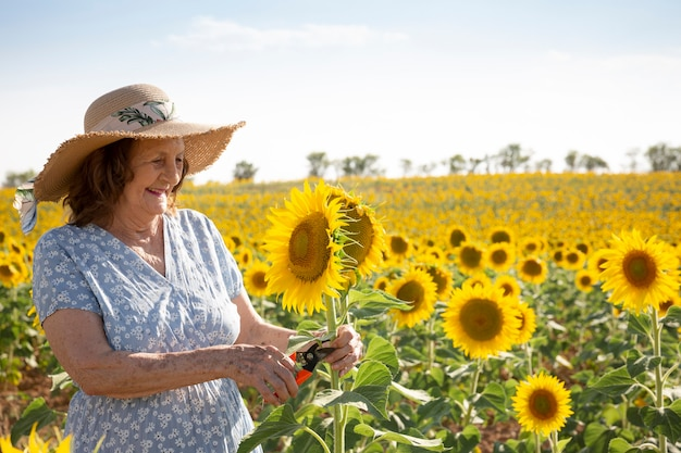 Femme âgée souriante avec un sécateur dans un champ de tournesol.