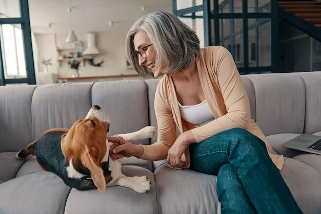 Femme âgée souriante en vêtements décontractés passant du temps avec son chien assis sur le canapé à la maison