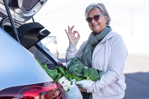Une femme âgée sourit après avoir acheté des légumes frais en les mettant dans le coffre de la voiture. signe positif avec la main pour une alimentation saine