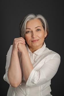 Une femme âgée sourit avec charme en inclinant légèrement la tête et les mains jointes près du visage. belle dame en chemise blanche isolée sur fond gris