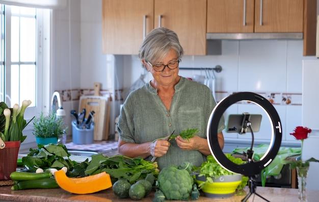 Une femme âgée en streaming en ligne suit un cours de cuisine végétarienne. table de cuisine à la maison pleine de légumes sains