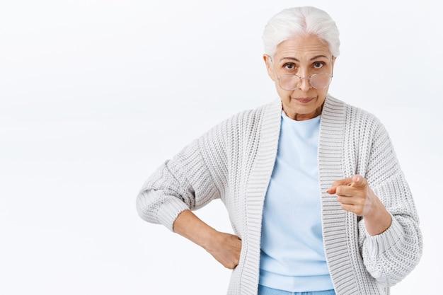 Femme âgée stricte, sérieuse, mécontente et en colère, grand-mère déçue du mauvais comportement, fils réprimandé, doigt tremblant affligé et dérangé, sourire narquois dérangé, avertissement de ne pas jouer de tours