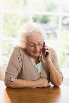 Femme âgée téléphonant à la maison
