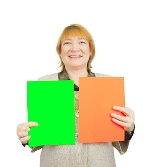 Femme âgée tenant des affiches rouges et vertes vides
