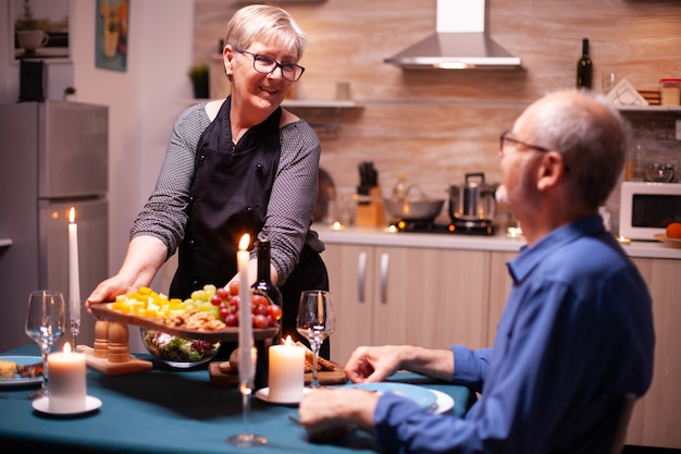 Femme âgée tenant une assiette en bois avec et regardant son mari pendant le dîner de fête. vieux couple de personnes âgées parlant, assis à table dans la cuisine, savourant le repas, célébrant leur anniversaire.