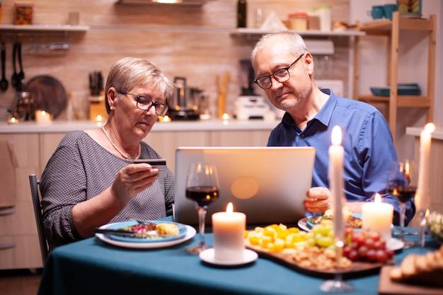 Femme âgée tenant une carte de crédit tout en utilisant un ordinateur portable avec son mari pour faire du shopping. des personnes âgées assises à table, naviguant, utilisant la technologie, internet, célébrant leur anniversaire.