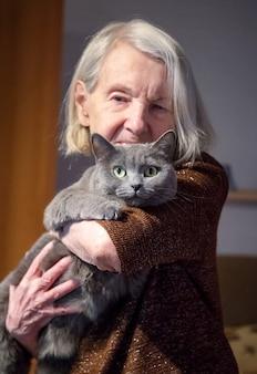 Une femme âgée tenant un chat regarde la caméra.