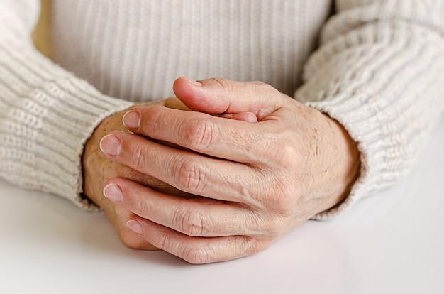 Une femme âgée tenant la main ensemble sur le mur blanc.