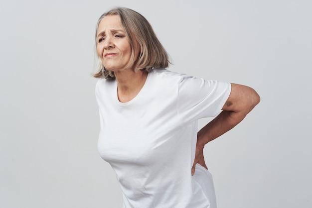 Femme âgée tenant son traitement de la douleur au bas du dos. photo de haute qualité
